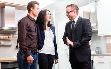 Dargestellt wird ein Gespräch zwischen zwei Kaufinteressenten und einem Verkäufer.