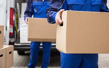 Dargestellt werden zwei Personen, welche Pakete aus einem Transporter laden.