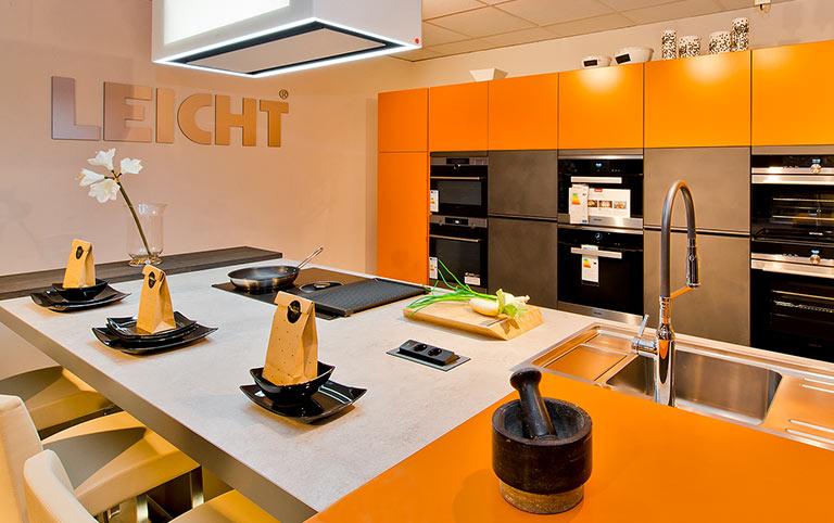 Dargestellt wird eine Orangefarbene Küche (in der Ausstellung) der Marke Leicht