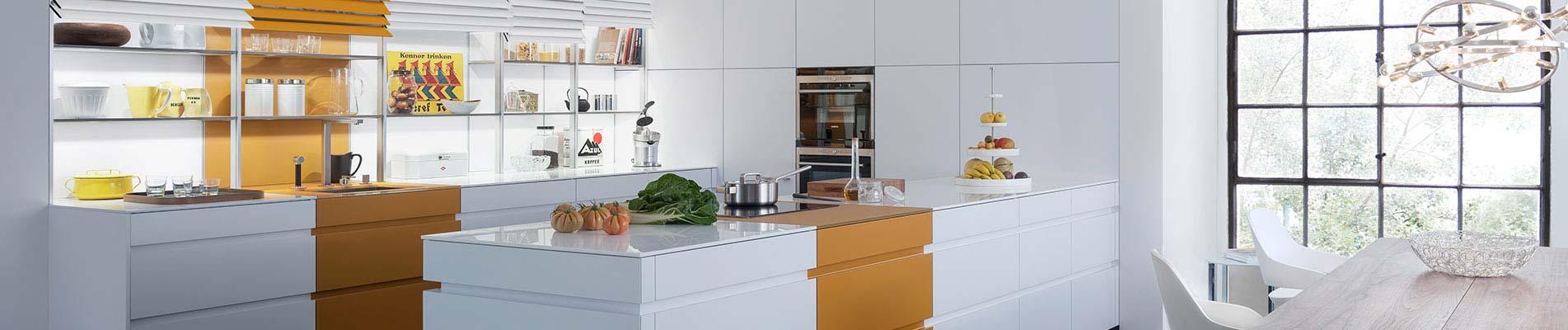 Weiße Küche mit orangenen Applikationen der Marke Leicht